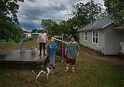 """Dennis Mann, left, and his wife Deborah stand outside their storm cellar with neighbor Mathew Tettleton moments after a tornado warning ended on Monday May 20, 2013, in Montague, Texas. When I asked Deborah if they had gone to the cellar she laughed and said, """"I did, but Dennis stayed out here to make sure his truck didn't blow away."""""""