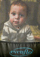 """One-year-old Michael Porter sits in his playpen on March, 9, 2016, facing a tear in the mesh netting that was caused by a stray bullet which landed in the base of the crib after first striking a metal chair and sliding glass door in his uncle's Las Cruces home on Sunday, March 6, 2016. Las Cruces Police officer Keegan Arbogast ruled out foul play and advised the family that the bullet likely came from """"people shooting their rifles out in the desert."""""""