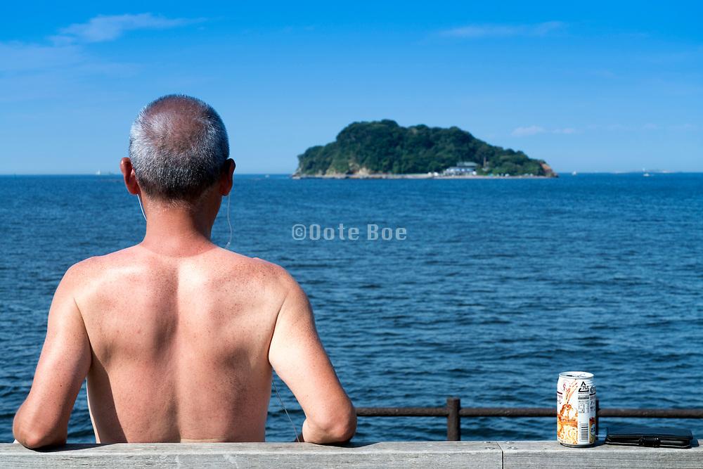 man relaxing at Umikaze park, Yokosuka with Tokyo Bay and Sarushima Island