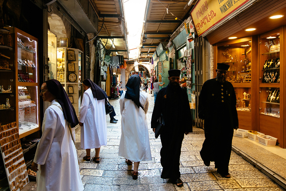 Christian nuns and priests are seen at the market near the Church of the Holy Sepulchre in the Old City of Jerusalem, on August 28, 2017.