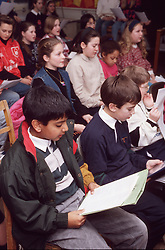 Multiracial group of children in junior school assembly,