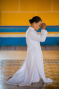 "29 MARCH 2012 - TAY NINH, VIETNAM:  A Cao Dai adherent prays in the main hall of the Cao Dai Holy See in Tay Ninh, Vietnam. Cao Dai (also Caodaiism) is a syncretistic, monotheistic religion, officially established in the city of Tây Ninh, southern Vietnam in 1926. Cao means ""high"" and ""Dai"" means ""dais"" (as in a platform or altar raised above the surrounding level to give prominence to the person on it). Estimates of Cao Dai adherents in Vietnam vary, but most sources give two to three million, but there may be up to six million. An additional 30,000 Vietnamese exiles, in the United States, Europe, and Australia are Cao Dai followers. During the Vietnam's wars from 1945-1975, members of Cao Dai were active in political and military struggles, both against French colonial forces and Prime Minister Ngo Dinh Diem of South Vietnam. Their opposition to the communist forces until 1975 was a factor in their repression after the fall of Saigon in 1975, when the incoming communist government proscribed the practice of Cao Dai. In 1997, the Cao Dai was granted legal recognition. Cao Dai's pantheon of saints includes such diverse figures as the Buddha, Confucius, Jesus Christ, Muhammad, Pericles, Julius Caesar, Joan of Arc, Victor Hugo, and the Chinese revolutionary leader Sun Yat-sen. These are honored at Cao Dai temples, along with ancestors.    PHOTO BY JACK KURTZ"