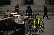 A person lies on a bench reading an Evening Standard newspaper carrying a headline about the Guinness trial, on 27th May 1991, in the City of London, England. The Guinness share-trading fraud was a major business scandal of the 1980s. It involved the manipulation of the London stock market to inflate the price of Guinness shares to thereby assist Guinnesss £4 billion takeover bid for the Scottish drinks company Distillers. In May 1991, Saunders and his co-accused appealed against their convictions.