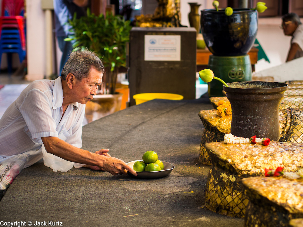 "15 AUGUST 2014 - BANGKOK, THAILAND:   A man prays and makes an offering of oranges at the base of standing Buddha statue in Wat Intharawihan. Wat Intharawihan (also called Wat Intharavihan) is a Buddhist temple located in the Nakhon District of Bangkok, Thailand. It was built at the beginning of the Ayutthaya period and was originally called Wat Rai Phrik. The best known feature of the temple is a 32 meter high (105 feet), 10 meter wide (33 feet) standing Buddha referred to as Luang Pho To or ""Phra Si Ariyamettrai."" It took over 60 years to complete and is decorated in glass mosaics and 24-carat gold. The topknot of the Buddha image contains a relic of Lord Buddha brought from Sri Lanka.      PHOTO BY JACK KURTZ"