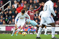 Ki Sung-Yueng of Swansea City competing with Enner Valencia of West Ham United. Barclays Premier league match, West Ham Utd v Swansea city at the Boleyn ground, Upton Park in London on Sunday 7th December 2014.