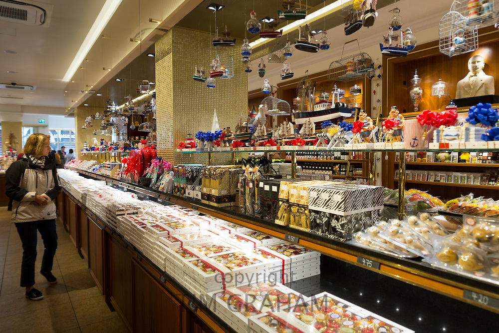 Marzipan sweets and candy on display and shopper inside J.G. Niederegger shop in Lubeck - famous for marzipan, Northern Germany