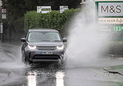 © Licensed to London News Pictures. 23/09/2018. Leatherhead, UK. A car splashes through partially flooded roads in Leatherhead, Surrey - as heavy rain hits parts of the south. Warmer temperatures are expected in a few days.  Photo credit: Peter Macdiarmid/LNP
