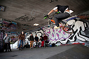 A walk along the River Thames on the Southbank in London. A group of BMX riders hanging out at the under-croft. This area is very popular especially on the weekends for Londoners to walk and see different arts, culture and entertainment. Here, at the under-croft it is seen at the British home to urban culture, street sports and graffiti.