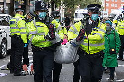 Metropolitan Police officers arrest a climate activist from Extinction Rebellion who had occupied the street outside the Department of Transport in protest against roadbuilding on 3 September 2020 in London, United Kingdom. Extinction Rebellion activists are attending a series of September Rebellion protests around the UK to call on politicians to back the Climate and Ecological Emergency Bill (CEE Bill) which requires, among other measures, a serious plan to deal with the UK's share of emissions and to halt critical rises in global temperatures and for ordinary people to be involved in future environmental planning by means of a Citizens' Assembly.