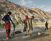 On the flat roof of their home, men shake off and fold ropes after carrying dry hay to their home and putting inside a barn accessible from the roof.  The traditional life of the Wakhi people, in the Wakhan corridor, amongst the Pamir mountains.