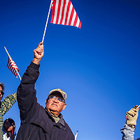 112614       Cable Hoover<br /> <br /> Jonah Jones, center, and other protesters wave flags at passing traffic during a protest march in Window Rock Wednedday.