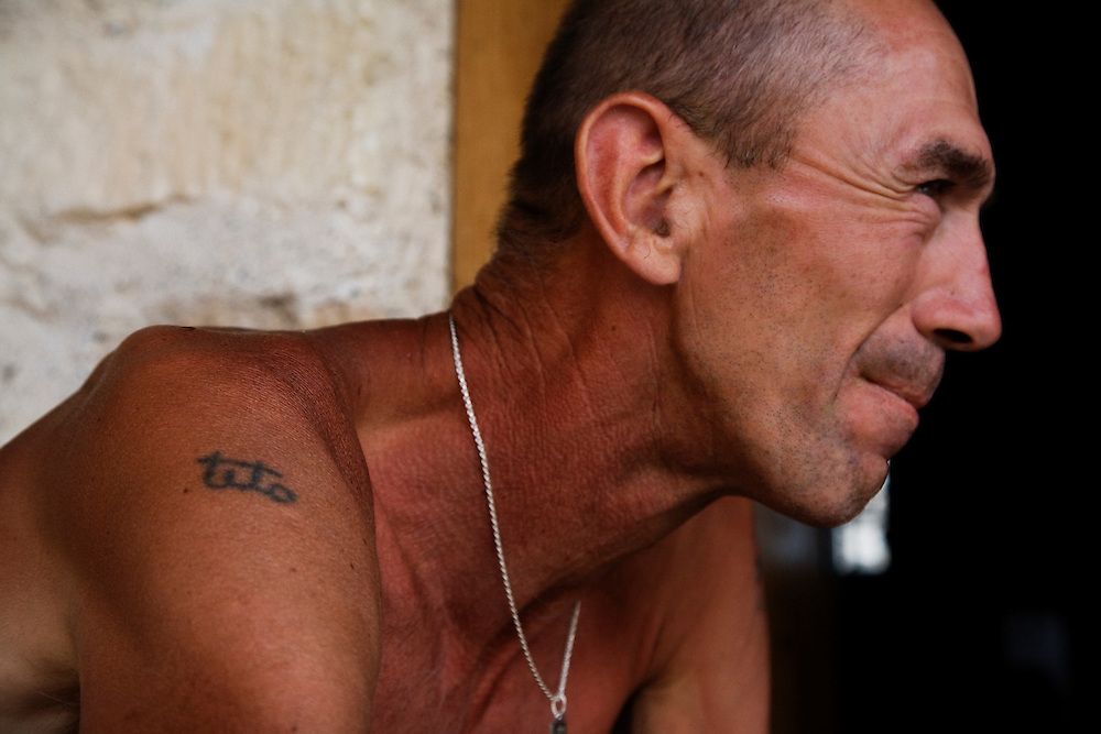 """Adem Mocca Pajevic and his tattoo of Tito...Divers and tourists at Mostar's famous Old Bridge (Stari Most) in Bosnia and Herzegovina. This bridge is the city and region's biggest tourist attraction and there are busses full of tourists coming in from Sarajevo and Dubrovnik, Croatia. For 25euros tourists can train to jump from the bridge themselves, under supervision from the """"professional"""" Mostar divers known as the Mostari. .."""