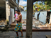 14 OCTOBER 2015 - BANGKOK, THAILAND: A man carries his baby past a destroyed home in the Wat Kalayanamit neighborhood. Fifty-four homes around Wat Kalayanamit, a historic Buddhist temple on the Chao Phraya River in the Thonburi section of Bangkok, are being razed and the residents evicted to make way for new development at the temple. The abbot of the temple said he was evicting the residents, who have lived on the temple grounds for generations, because their homes are unsafe and because he wants to improve the temple grounds. The evictions are a part of a Bangkok trend, especially along the Chao Phraya River and BTS light rail lines. Low income people are being evicted from their long time homes to make way for urban renewal.         PHOTO BY JACK KURTZ