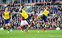 Burnley's Danny Ings attempts a bicycle kick to have a shot on goal under pressure from Arsenal's Nacho Monreal, left, and Arsenal's Francis Coquelin<br /> <br /> Photographer Chris Vaughan/CameraSport<br /> <br /> Football - Barclays Premiership - Burnley v  Arsenal - Saturday 11th April 2015 - Turf Moor - Burnley<br /> <br /> © CameraSport - 43 Linden Ave. Countesthorpe. Leicester. England. LE8 5PG - Tel: +44 (0) 116 277 4147 - admin@camerasport.com - www.camerasport.com