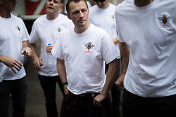 © Licensed to London News Pictures . 26/06/2017 . Manchester , UK . Fire-fighters wearing symbolic Manchester bee t-shirts walk from Manchester Central Fire Station to St Ann's Square in Manchester City Centre for a short ceremony and release of 22 doves , in commemoration of the 22 people killed in a murderous terrorist attack , carried out by Salman Abedi , following an Arina Grande concert at the Manchester Arena , on 22nd May 2017 . Local fire crews have expressed frustration after they were held back from attending to support other emergency services for nearly two hours after the bombing , on the night of the attack . Photo credit : Joel Goodman/LNP