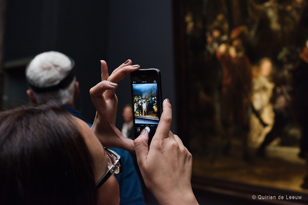 A visitor takes a photo with smartphone of the famous oil-painting Nachtwacht (Nightwatch) of the dutch painter Rembrandt van Rijn