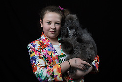 © Licensed to London News Pictures. 10/03/2016. Birmingham, UK. Hannah Furey with her Toy Poodle named Olivia at Crufts 2016 held at the NEC in Birmingham, West Midlands, UK. The world's largest dog show, Crufts is this year celebrating it's 125th anniversary. The annual event is organised and hosted by the Kennel Club and has been running since 1891. Photo credit : Ian Hinchliffe/LNP