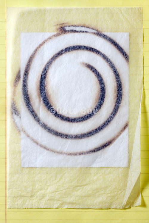 blank yellow lined notepad and white paper burned with a circular imprint