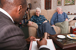 Professional with elderly couple at home.
