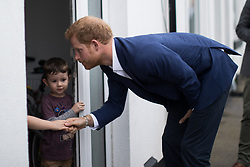 © Licensed to London News Pictures . 04/09/2017 . Manchester , UK . Prince Harry shakes hands with resident KOBI FLORES (six) as his younger brother DAMASO FLORES (four) looks on , during a visit to the Walking With the Wounded ( WWTW) hub on Canada Street , Newton Health .  WWTW helps ex-service personnel with physical or mental health needs make the transition back to civilian life . The street was subject to an episode of DIY SOS when people gave their time and resource to help redevelop the houses . Photo credit : Joel Goodman/LNP