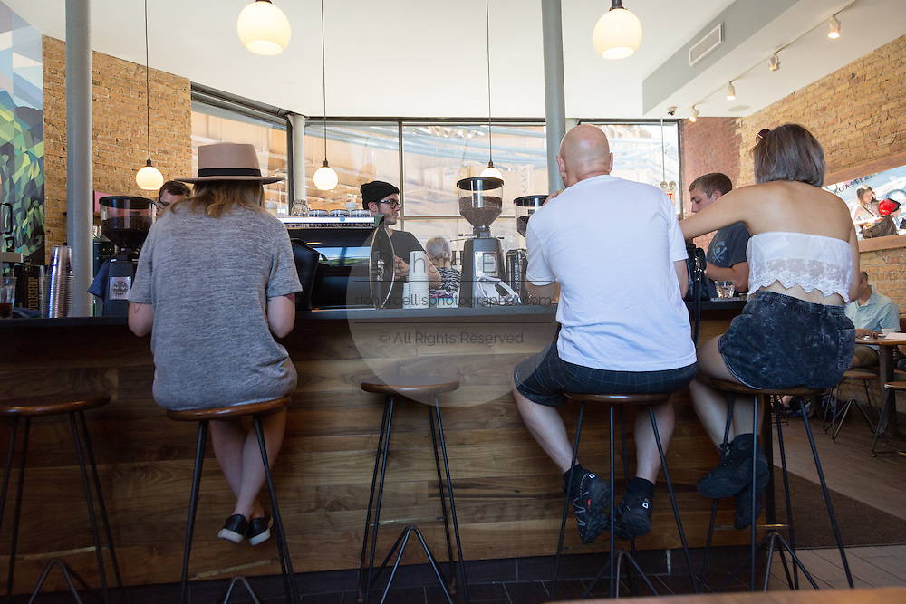 Customers sitting at the bar in the trendy Pure Black coffee shop in the hip Wicker Park neighborhood in the West Town community in Chicago, Illinois, USA