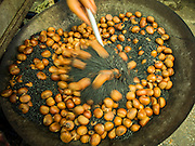 25 APRIL 2014 - MAE SAI, CHIANG RAI, THAILAND: Roasting chestnuts by hand in Mae Sai, Thailand, which borders Myanmar. PHOTO BY JACK KURTZ