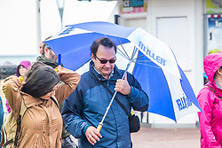 © Licensed to London News Pictures. 16/06/2019. Brighton, UK. A member of the public shelters from the rain as cold and wet weather is hitting Brighton and Hove. Photo credit: Hugo Michiels/LNP