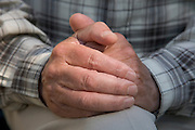 folded hands of an elderly man