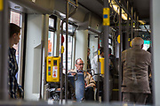 Elderly people travel onboard an electric tram operated by De Lijn in Ghent, Belgium.