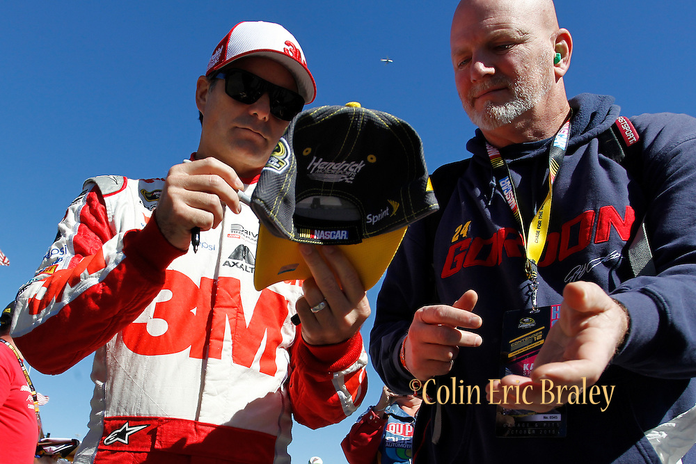 NASCAR Sprint Cup Series auto racing driver Jeff Gordon, left, signs autographs before a practice at Kansas Speedway in Kansas City, Kan., Saturday, Oct. 16, 2015. (AP Photo/Colin E. Braley)
