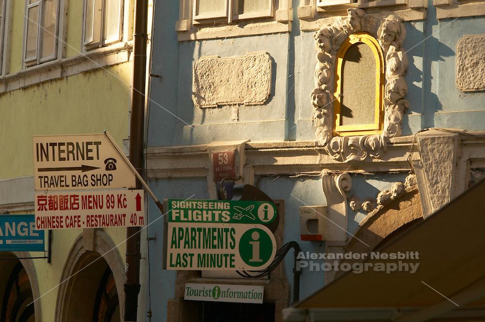 Czeck Republic - Prague, Signs on busy Mosteká in Malá Strana advertise travelers services.