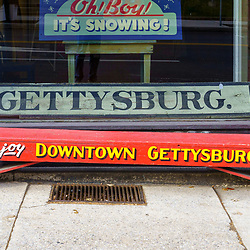 Gettysburg, PA / USA - December 7, 2019:  A red painted Bench with writing that invites to Enjoy Downtown Gettysburg in front of a store.