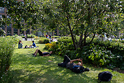 Londoners relax and sleep on the grass opposite St Pauls Cathedral, on 21st July 2021, in the City of London, England.