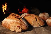 Freshly baked bread by a stone oven. Flames in the background