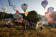 Families watch the mass lift-off by balloons at Bristols annual fiesta at Ashton Court, UK. Taking off into early morning summer skies above England's southwest City, the airships rise from the heat of hot air burners. Crowds from across the city arive with BBQs and picnics and children to sit and wait for the green smoke that signals a Go. Once airbourne, the balloons start to climb only a short distance, to land a few hundred metres away on this particular morning's stll air conditions. The 37th Bristol International Balloon Fiesta is billed as Europe's largest (and free) ballooning event. Bristol's local ballooning entrepreneur hero is Don Cameron whose balloons are known worldwide.