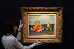 © Licensed to London News Pictures. 12/04/2013. London, UK. Gallery assistant mounts Paul Cézanne's 'Les Pommes.' painting with an estimated value of between 25 - 35 million USD for the upcoming New York auctions. Highlights from Sotheby's New York auctions of Impressionist and Modern Art and Contemporary Art will be exhibited to the public from 12-16 April at  Sotheby's London New Bond Street galleries..Photo credit : Peter Kollanyi/LNP