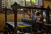 Female weaver making textiles at the Pelangi traditional weaving workshop in Sideman valley, Bali, Indonesia on 13th June 2018 in Bali, Indonesia. The Sideman region is known for weaving, especially making patterned ikat endek and songket cloth.