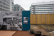 """An outdoor exhibition panel near the former Checkpoint Charlie, the former border between Communist East and West Berlin during the Cold War. The Berlin Wall was a barrier constructed by the German Democratic Republic (GDR, East Germany) starting on 13 August 1961, that completely cut off (by land) West Berlin from surrounding East Germany and from East Berlin. The Eastern Bloc claimed that the wall was erected to protect its population from fascist elements conspiring to prevent the """"will of the people"""" in building a socialist state in East Germany. In practice, the Wall served to prevent the massive emigration and defection that marked Germany and the communist Eastern Bloc during the post-World War II period."""