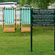 Two park deckchairs and tarifs sign in Hyde Park, London
