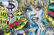 A colorful wall mural on Melrose Ave. in Los Angeles, California depicts a stylized woman with money floating across  the mural.