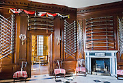 "Guns and swords decorate the foyer of the Governor's Palace on Duke of Gloucester Street in Colonial Williamsburg, the historic district of the city of Williamsburg, Virginia, USA. Williamsburg was colonial Virginia's capital from 1699 to 1780 and a center of education and culture. The capital straddled the boundary of two of the original shires of Virginia, James City Shire (now James City County), and Charles River Shire (now York County). Here, Thomas Jefferson, Patrick Henry, James Monroe, James Madison, George Wythe, Peyton Randolph, and dozens more helped mold democracy in the Commonwealth of Virginia and the United States. Motto: ""that the future may learn from the past.""  The Historic Area exhibits colonial houses and American Revolutionary War history. Prominent buildings in Colonial Williamsburg include the Raleigh Tavern, the Capitol, The Governor's Palace, and Bruton Parish Church. Interpreters work, dress, and talk as they did in the era, teaching visitors. The 301-acre Historic Area is located immediately east of the College of William and Mary, which was founded at Middle Plantation in 1693. The new College, long a desire of the colonists, was a key factor in the establishment of the town as capital of Virginia in 1698 and its renaming for King William III of England shortly thereafter.  Jamestown and Yorktown, the other two points of the Historic Triangle, are linked to Colonial Williamsburg by the National Park Service's bucolic Colonial Parkway."