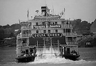 Lexie Palmore pilots the Delta Queen steamboat down the Ohio River, June, 1977.  She was the first female to become a riverboat pilot trainee, completing courses at the National River Academy in Helena, Arkansas.  She began her interest in riverboating as a passenger on the Delta Queen, later becoming a cabin maid.  She now pursues her life-long interest in painting from her home in Leadville, Colorado.