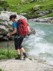 Woman hiking in the High Pyrenees walking on river shore of Gaube d'Estaube, France