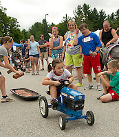 Kalissa Mooney is cheered by the crowd to keep her momentum going as Lizzie Fleming adds a couple bricks to her load during the children's pedal tractor pull event at Belmont Old Home Day festivities Saturday morning.  (Karen Bobotas/for the Laconia Daily Sun)