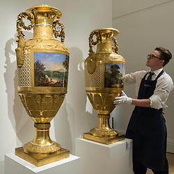 """© Licensed to London News Pictures. 01/06/2018. LONDON, UK. A Sotheby's technician presents """"A pair of monumental gilt-bronze mounted porcelain vases"""", 1825, by Imperial Porcelain Factory, St Petersburg (Est. GBP1.0-1.5m) at a preview of the Russian Pictures and Russian Works of Art, Fabergé & Icons sale which will take place at Sotheby's, New Bond Street on 5 June.  Photo credit: Stephen Chung/LNP"""