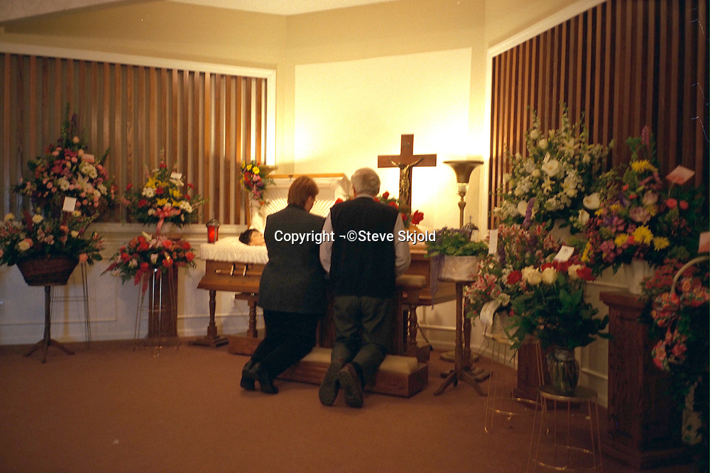 Couple kneeling before open coffin at a wake.  Brooklyn Center Minnesota USA
