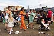 A gruop of flamboyantly dressed women, one with a baby and pram, on the fair ground at Appleby Horse Fair, the biggest gathering of Gypsies and travellers in Europe, on 14th August, 2021 in Appleby, United Kingdom. Appleby Horse Fair attracts thousands from Gypsy, Romany, and traveller communities annually, making it the biggest gathering of its kind in Europe. Generally held for a week every June, the fair was postponed in 2020 and pushed forward to August in 2021 due to Coronavirus.