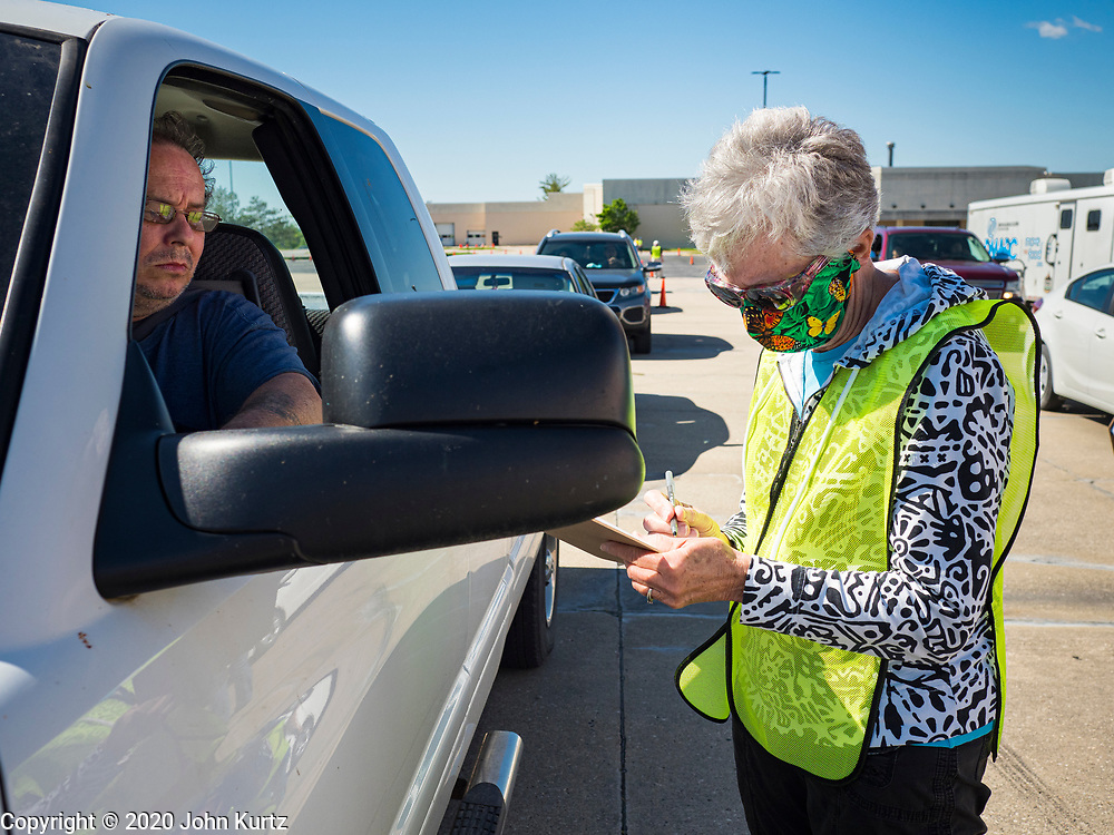 29 MAY 2020 - DES MOINES, IOWA: PHYLLIS JOHNSON, right, a volunteer, checks people in during a produce distribution in a mall parking lot in Des Moines. The Des Moines Area Religious Council (DMARC) and Capitol City Fruit from Norwalk, IA, gave away 1,800 boxes of fresh produce with a mix of vegetables and fruit. The boxes contain enough produce to feed a family of four for a week. The produce was provided by the USDA Farmers to a Families food program. Because of the COVID-19 pandemic, the unemployment rate in Iowa hit 10.2% in May, the highest unemployment rate ever recorded in Iowa and food insecurity in Iowa is impacting communities throughout the state.         PHOTO BY JACK KURTZ