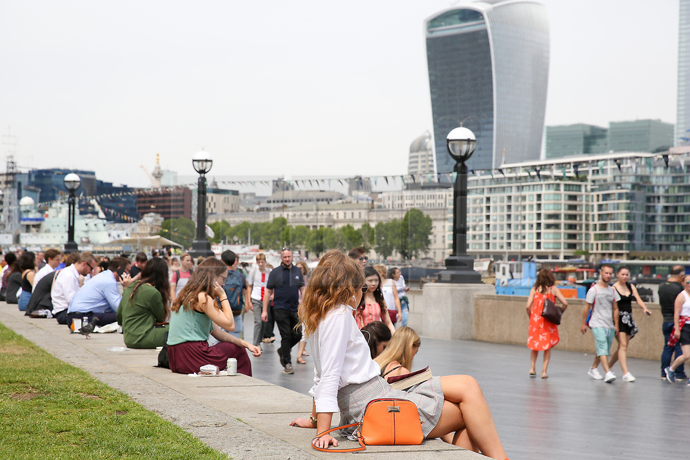 © Licensed to London News Pictures. 17/07/2019. London, UK. City workers and tourists enjoy the warm weather near Tower Bridge at lunchtime. According to the Met Office, rain is forecast across the country during the next few days. Photo credit: Dinendra Haria/LNP