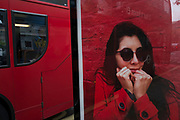 Woman on a bus shelter advertising board with her hands to her face as if scared of the red London bus traffic that is passing in London, England, United Kingdom.